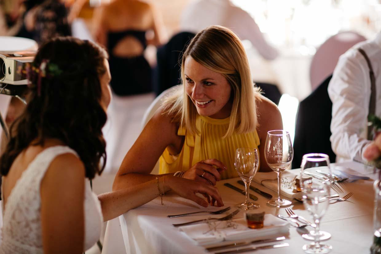 Braut sitzt mit der Trauzeugin am Tisch und unterhält sich