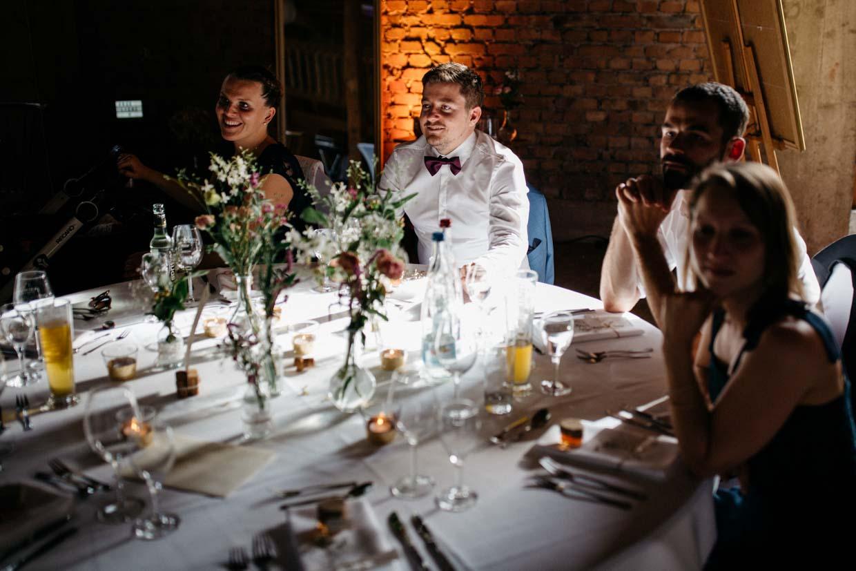 Hochzeitsgäste sitzen am runden Tischund schauen gespannt nach vorne