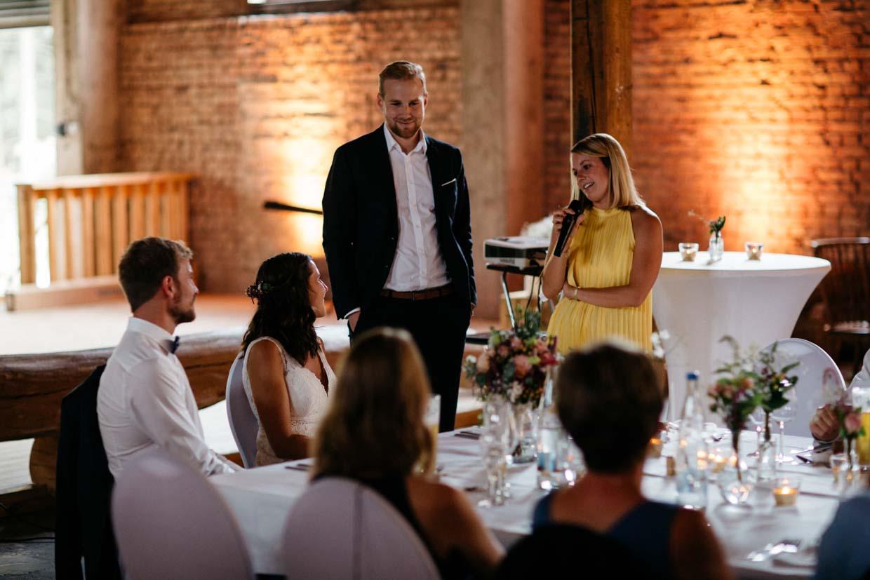 Hochzeitsgäste halten eine Rede vor dem Brautpaar