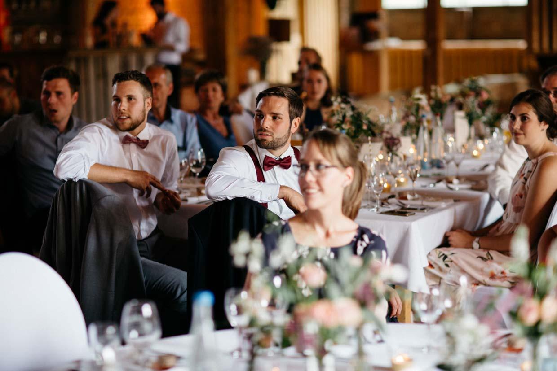 Hochzeitsgäste sitzen an ihren Tischen und schauen gespannt nach vorne