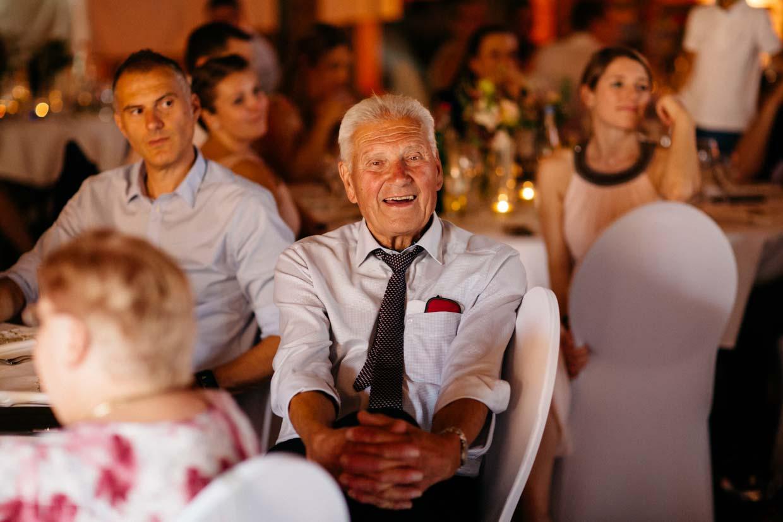 Älterer Hochzeitsgast sitzt und lächelt freundlich in die Kamera