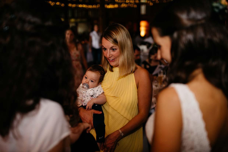 Hochzeitsgäste stehen beisamen mit einem Baby in der Hand