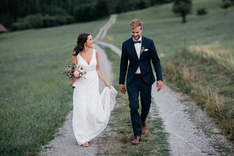 Brautpaar läuft einen Feldweg entlang