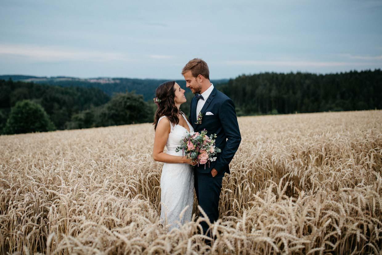 Brautpaar steht im Kornfeld und schaut sich an
