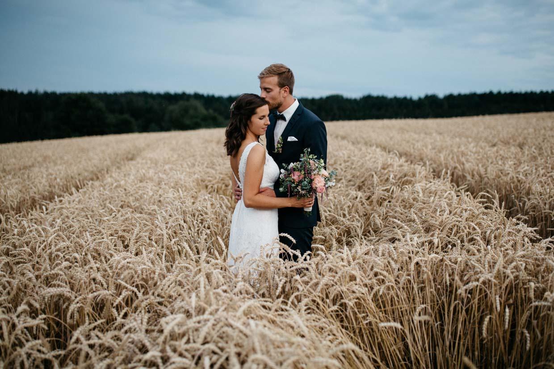 Brautpaar steht im Kornfeld und Bräutigam gibt der Braut einen Kuss auf die Stirn