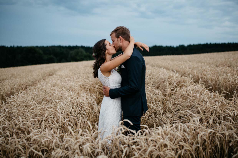 Brautpaar steht im Kornfeld und küsst sich