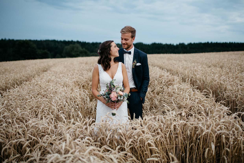 Brautpaar steht hintereinander im Kornfeld und schaut sich an