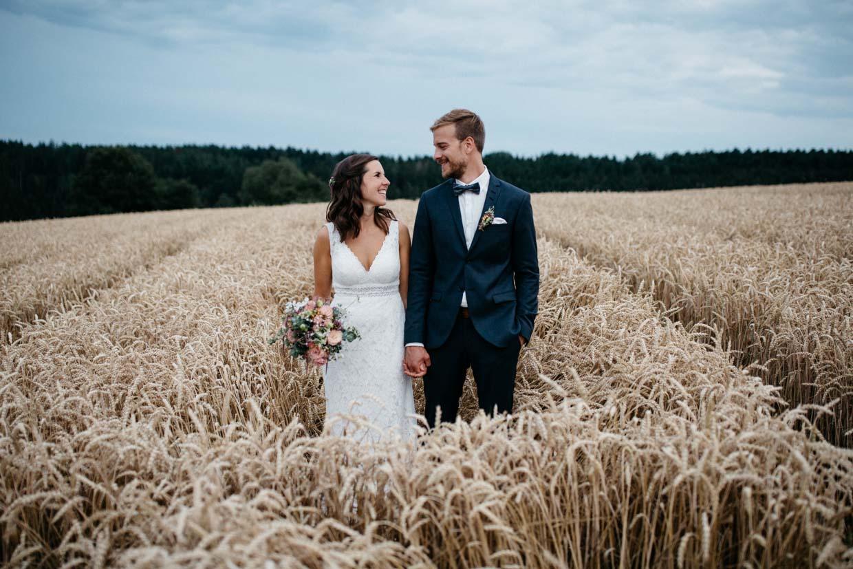 Brautpaar steht nebeneinander im Kornfeld und lacht gemeinsam