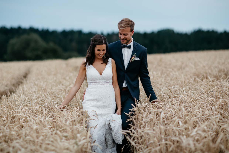 Brautpaar geht gemeinsam durch ein Kornfeld