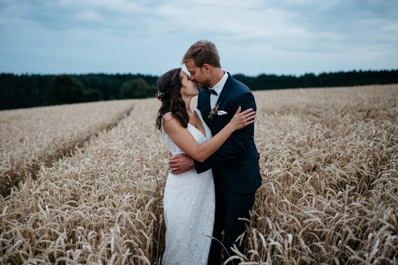 Brautpaar steht im Kornfeld, umarmt und küsst sich