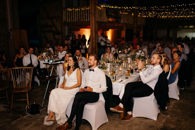 Brautpaar und Hochzeitsgäste sitzen und schauen sich eine Beamershow an