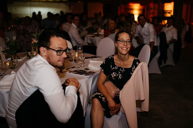 Hochzeitsgäste sitzen am Tisch und lachen freundlich