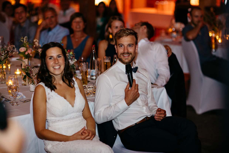 Brautpaar sitzt nebeneinander und Bräutigam hält das Mikrofon