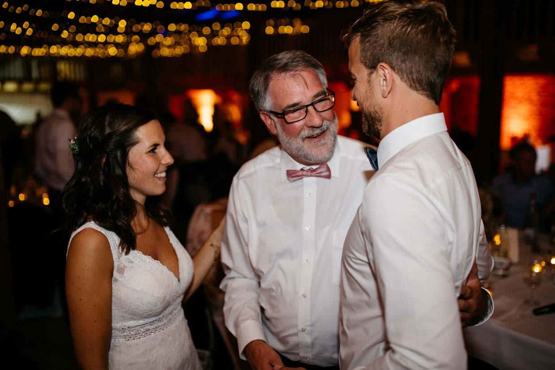 Brautpaar und Brautvater stehen glücklich nebeneinander