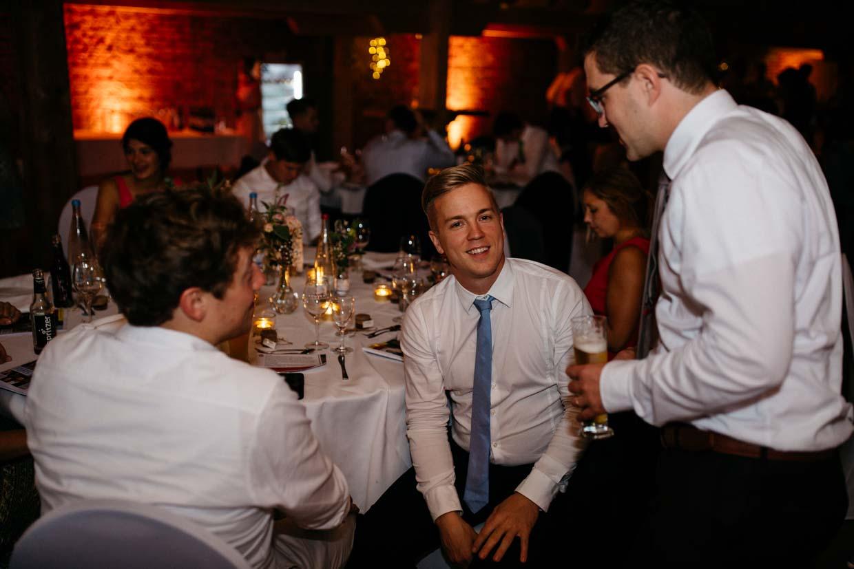 Hochzeitsgäste sitzen am Tisch und unterhalten sich