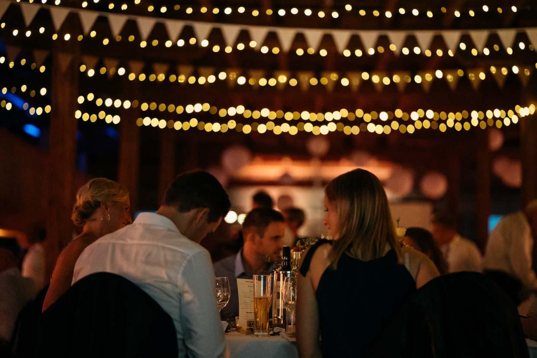 Hochzeitsgäste sitzen am Tisch und darüber hängen Lichterketten, die unscharf fotografiert sind