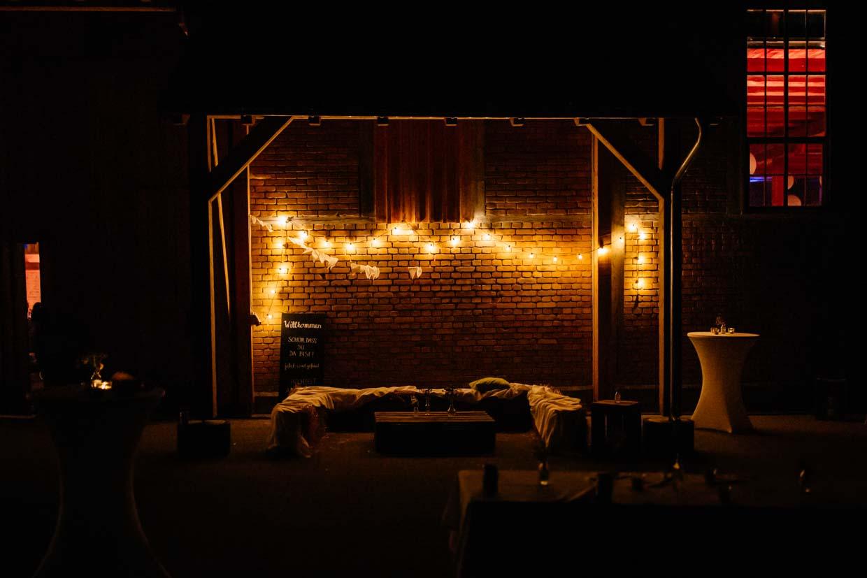 Nachtaufnahme des Fabrikgebäudes mit Lichterkette an der Wand
