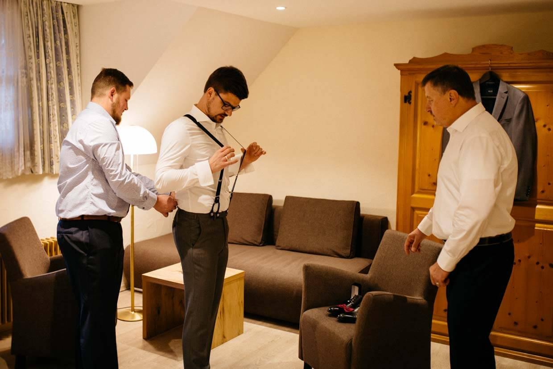 Bräutigam, Trauzeuge und Bräutigamsvater beim Anziehen