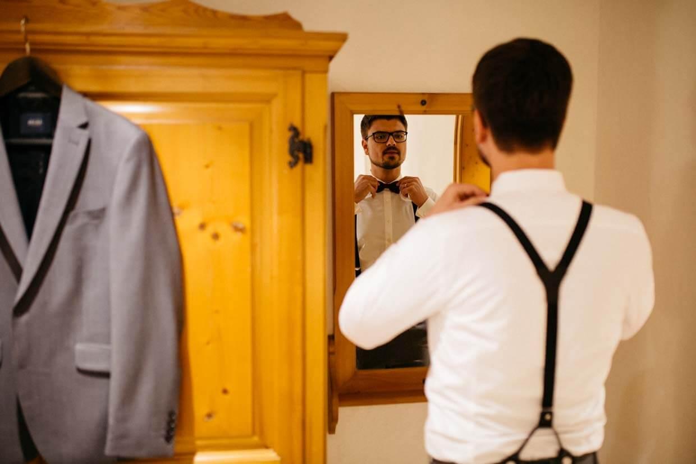 Bräutigam richtet Fliege vor dem Spiegel