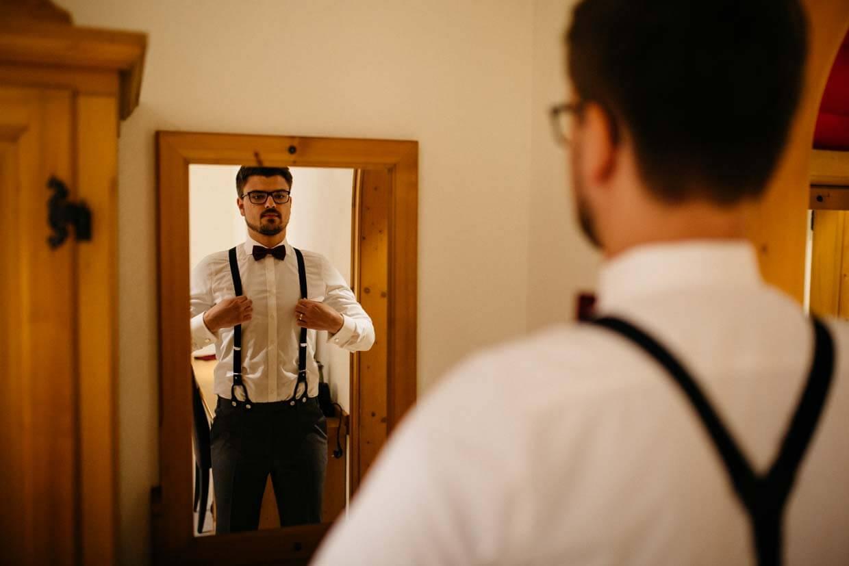 Bräutigam richtet seine Hosenträger vor dem Spiegel