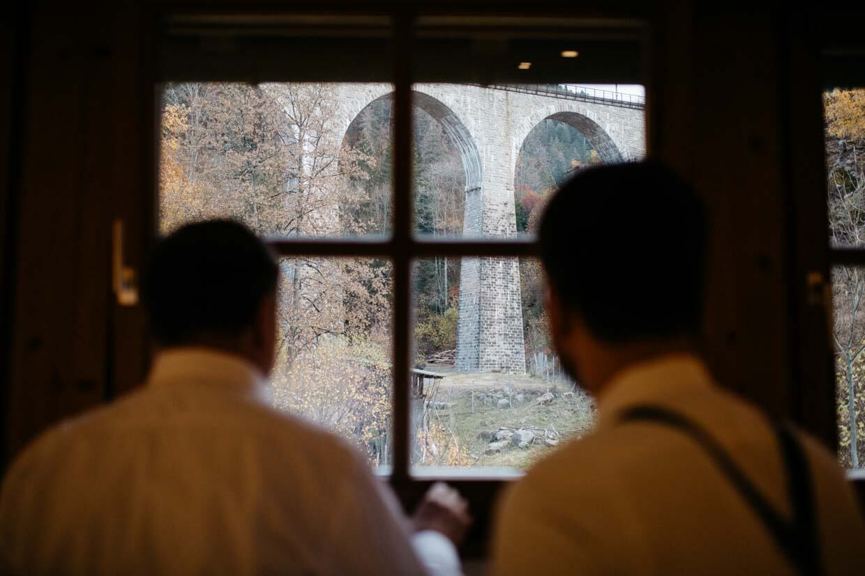 Bräutigam schaut mit Vater aus dem Fenster Richtung Viadukt