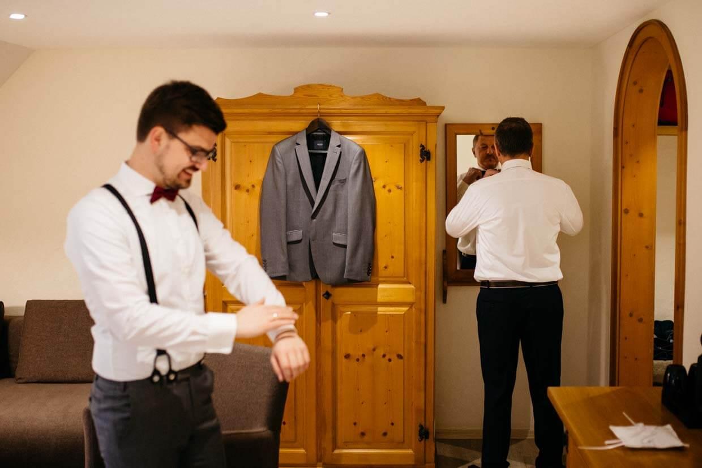 Bräutigamsvater richtet seine Fliege vor dem Spiegel
