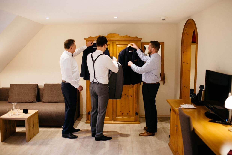 Bräutigam, Trauzeuge und Bräutigamsvater halten ihre Sakkos