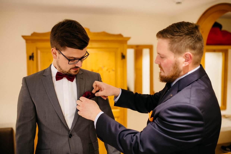 Trauzeuge steckt dem Bräutigam das Einstecktuch an
