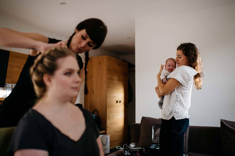 Trauzeugin hällt das Kind der Braut, während diese geschminkt wird