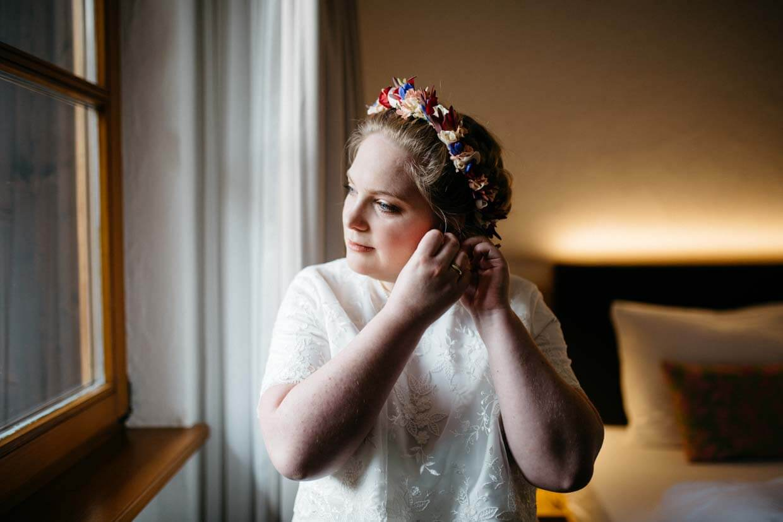 Braut legt sich die Ohrringe an