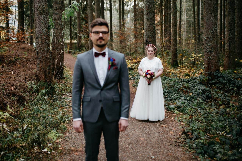 Braut steht beim First Look hinter dem Bräutigam