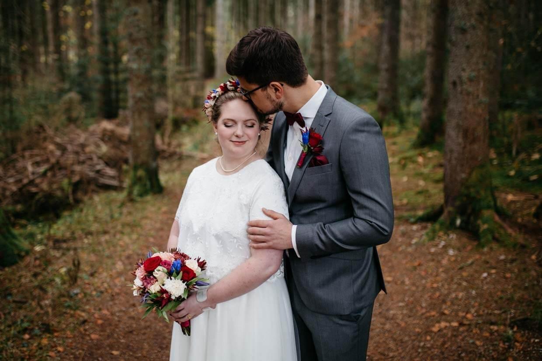 Brautpaar steht hintereinander und Bräutigam gibt der Braut einen Kuss auf die Stirn