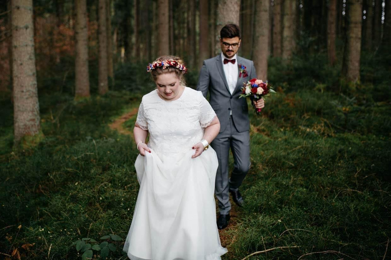 Brautpaar geht hintereinander einen Waldweg entlang