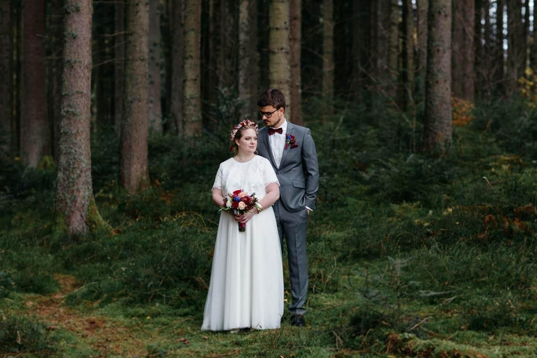 Brautpaar steht im Wald hintereinander