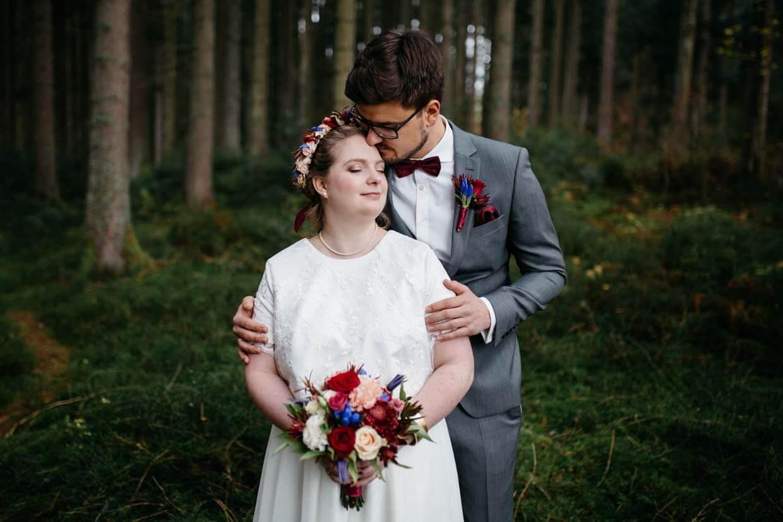 Brautpaar steht im Wald hintereinander und Bräutigam umarmt die Braut von hinten