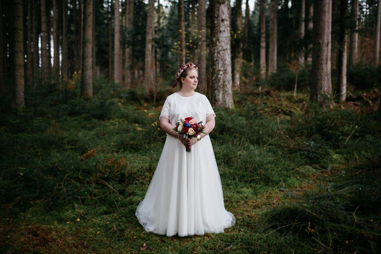 Braut steht alleine im Wald