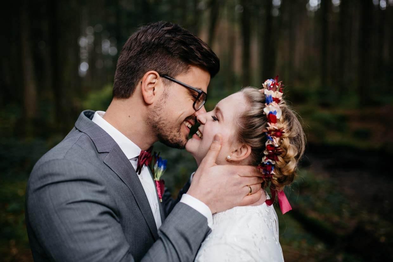 Bräutigam hält den Kopf der Braut und beide lachen