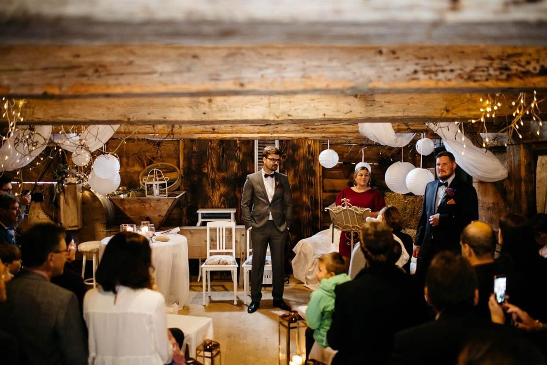 Bräutigam wartet auf die Braut vorne in der Scheune