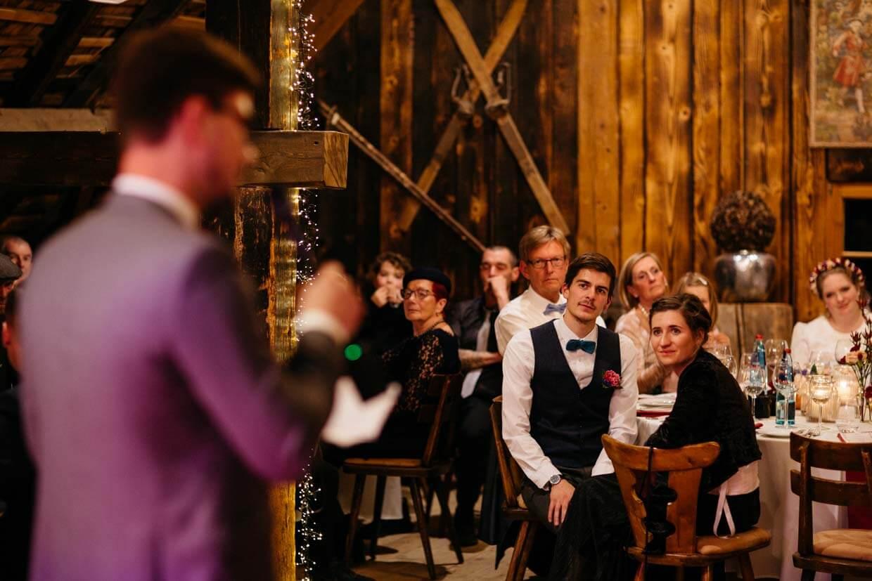 Hochzeitsgäste hören der Rede des Bräutigams zu
