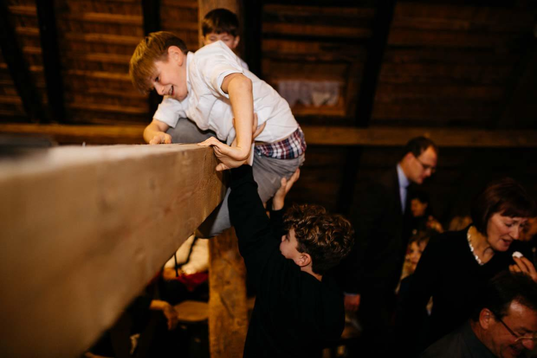 Jungs klettern Holzbalken hinauf