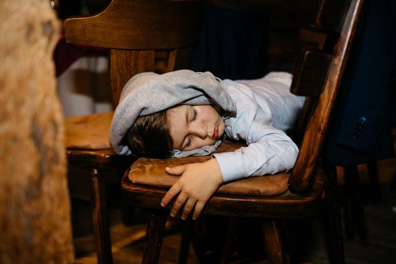 Kind liegt auf einem Stuhl und schläft